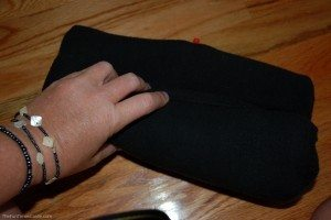 This photo shows how my choice for the best travel pillow folds into itself. After opening the red nozzle on the end, just start folding the pillow into itself to squeeze out the air. photo by Lynnette at TheFunTimesGuide.com