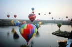 Hot air balloons over water in Texas.
