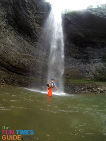 Playing underneath the waterfall at Ozone Falls while standing in the swimming hole.