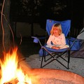 Sophie sitting by the campfire.