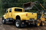 A bright yellow supertruck that doubles as a dump truck... it's an International CXT truck.